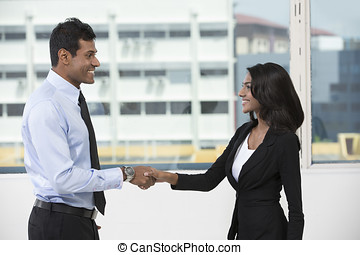 Indian business man and woman shaking hands - Indian...