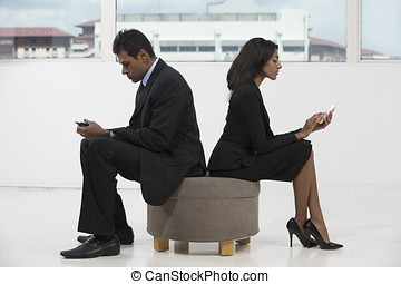 Indian business colleagues using smart phones. Indian...