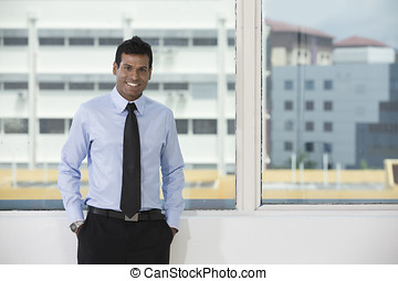 Indian business man standing by office window - Indian...
