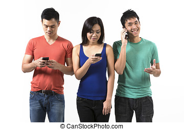 Group of young Chinese friends using their smartphones Happy...