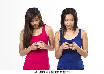 Group of young Chinese friends using their smartphones....