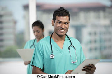 Male Indian doctor standing with his colleague - Portrait of...