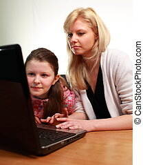 Mother Teaching her Child with a laptop
