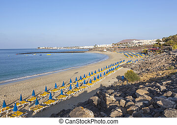 sandy beach in the morning with beach beds and umbrella -...