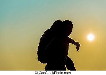 Lovely Couple piggy back ride on sunset in Silhouette  scene