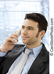 Businessman calling on phone - Young smiling businessman...
