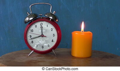 lighting yellow candle and clock