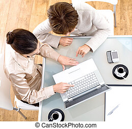 Businesswomen using laptop computer - High angle view of...