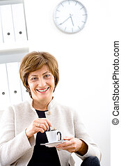 Businesswoman having coffee break - Senior businesswoman...