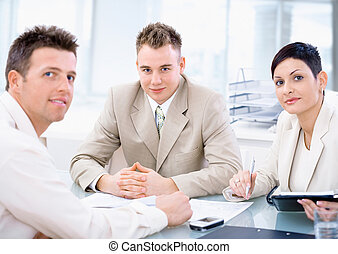 Businessteam of three working together, sitting around a...