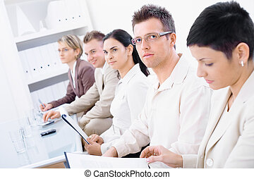 Business presentation - Business people sitting in a row and...