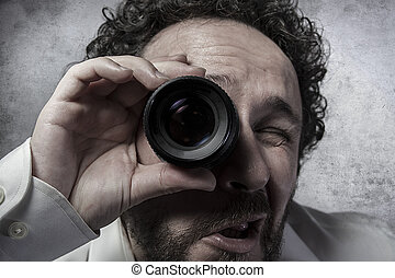 Businessman looking through a lens, man in white shirt with...