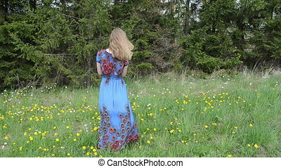 woman blow sowthistle - Woman dressed in long blue dress...