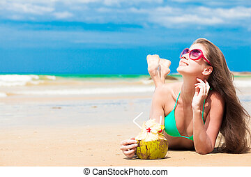Happy young  long haired woman in bikini with coconut lying on the beach