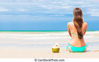 Happy young  long haired woman in bikini with coconut on the beach
