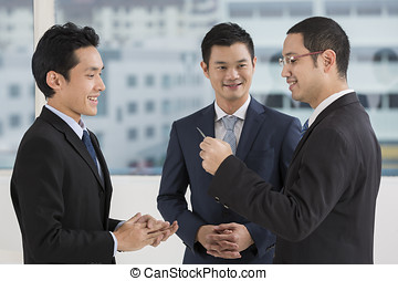 Two business men exchanging business cards. Caucasian and...
