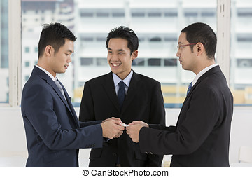 Two business men exchanging business cards Caucasian and...