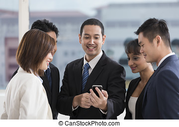 A group of business people looking at a smartphone - A multi...