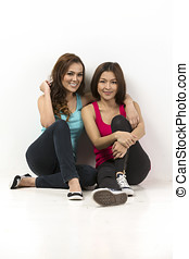Two happy Asian women sitting in front of a white wall.