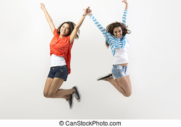 Two Asian women jumping - Two excited Asian women jumping in...