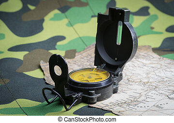 Military compass and map on a camouflage background