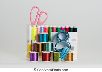 Coils with color threads, sewing needles, scissors