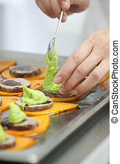 Close up of chef decorating sauce for appetizer
