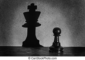Chess pawn standing in a spotlight that make a shadow of...