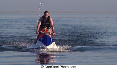 Jetskiing with Baby - The man rolls the small son on a jet...