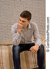 Worried young man sitting deep in thought with his fist to...