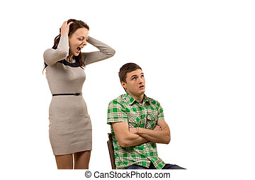 Young woman arguing with her boyfriend yelling at him as he...