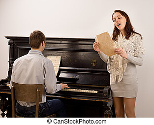 Young woman singing a solo song standing alongside a young...