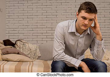 Depressed young man sulking after an argument