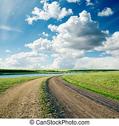 rural road in green grass and cloudy sky
