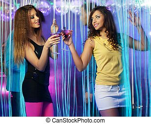 Happy young girls with drinks dancing at night club