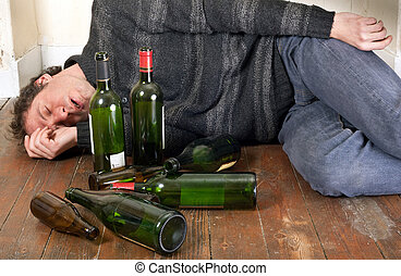 drunk man lying on the floor at home with many empty bottles