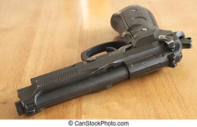 hand gun - a hand gun lying idle on a table