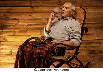 Senior man with smoking pipe sitting on rocking chair in...