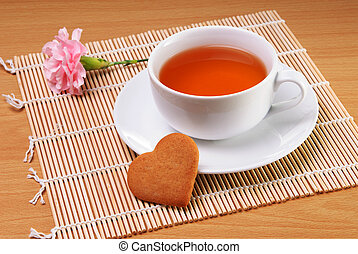 Cup of tea with heart shaped biscuit - White cup of tea with...
