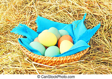 Basket of easter eggs on hay - Basket of colored easter eggs...