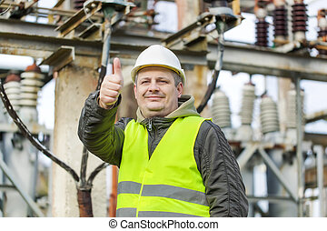 Electrician in electrical substation near to high-voltage...