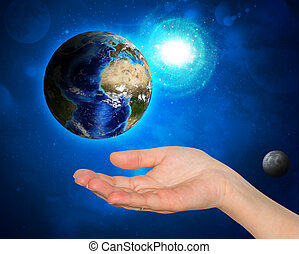 Hand holding earth. Starry sky in the background