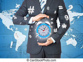 Man in suit holding alarm clock in hand. The concept of time