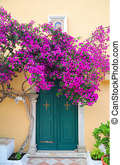 Greek monastery door with beautiful purple flowers