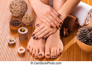 beautiful brown manicure and pedicure on the bamboo -...