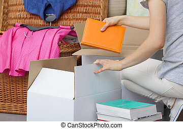 Colorful books packing - A woman packing colorful books into...