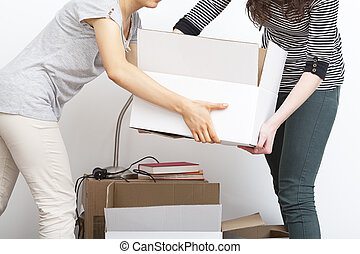 Moving boxes - Two women moving heavy and white boxes