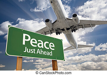 Peace Green Road Sign and Airplane Above with Dramatic Blue...