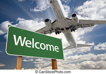 Welcome Green Road Sign and Airplane Above with Dramatic...
