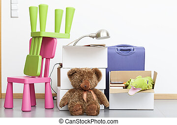 Kids stuff and colorful furniture packed before moving
